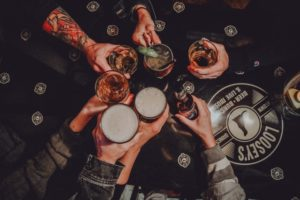 many hands holding beverages over a table with the Loosey's logo on it
